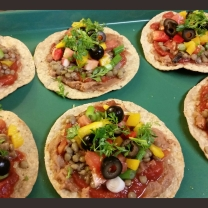 A tostada topped with refried beans, salsa, lentils, tomatoes, yellow peppers, olives, green onions, and cilantro. Baked in 250 degree oven for about 10 minutes.